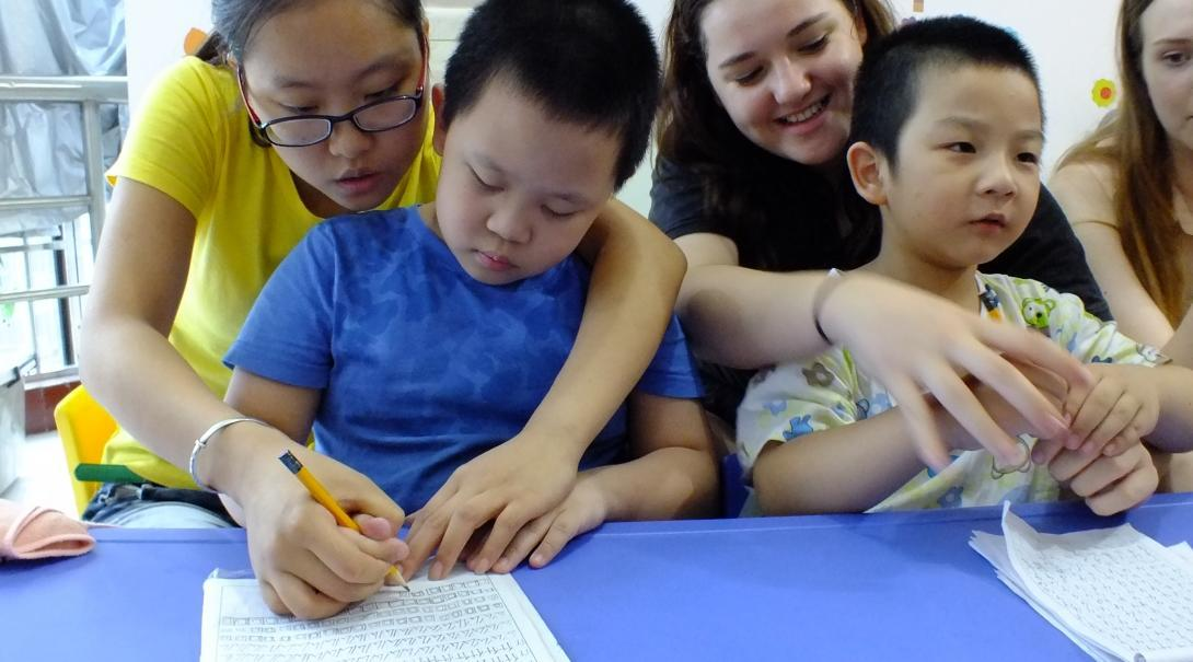 Two female Childcare volunteers working with kids in China help two young boys practice writing in English at a kindergarten.